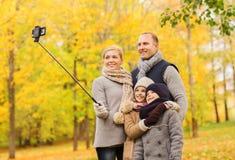 Familia feliz con smartphone y monopod en parque Fotografía de archivo