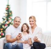 Familia feliz con smartphones Fotos de archivo