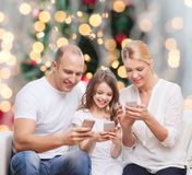 Familia feliz con smartphones Imágenes de archivo libres de regalías