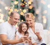 Familia feliz con smartphones Imagen de archivo libre de regalías