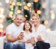 Familia feliz con smartphones Fotos de archivo libres de regalías