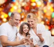 Familia feliz con smartphones Imagenes de archivo