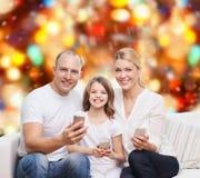 Familia feliz con smartphones Imagen de archivo
