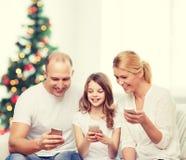 Familia feliz con smartphones Foto de archivo libre de regalías