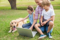Familia feliz con su perro usando el ordenador portátil Imágenes de archivo libres de regalías