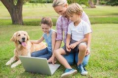 Familia feliz con su perro usando el ordenador portátil Foto de archivo