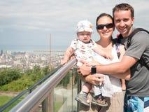 Familia feliz con un bebé hermoso que mira la ciudad de la gran altura de las montañas Foto de archivo libre de regalías
