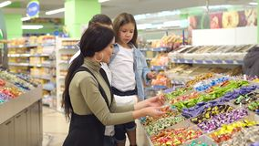 Familia feliz con un caramelo y los dulces de la compra del niño en el supermercado Cámara lenta almacen de video