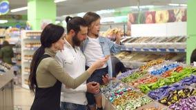 Familia feliz con un caramelo y los dulces de la compra del niño en el supermercado Cámara lenta almacen de metraje de vídeo