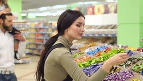 Familia feliz con un caramelo y los dulces de la compra del niño en el supermercado almacen de metraje de vídeo