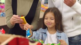 Familia feliz con un caramelo y los dulces de la compra del niño en el supermercado Primer metrajes