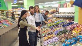 Familia feliz con un caramelo y los dulces de la compra del niño en el supermercado metrajes