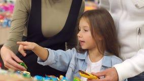 Familia feliz con un caramelo y los dulces de la compra del ni?o en el supermercado Primer metrajes