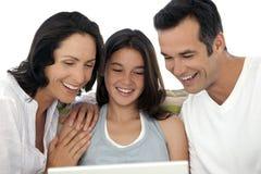 Familia feliz con un niño que usa el ordenador portátil Imagen de archivo