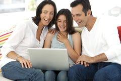 Familia feliz con un niño que usa el ordenador portátil Foto de archivo