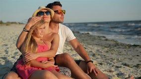 Familia feliz con una hija el las vacaciones que se sientan en la playa Padres sonrientes en gafas de sol con un niño que disfrut almacen de metraje de vídeo