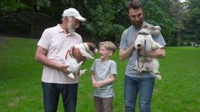 Familia feliz de abuelo y de hijo del padre con el perro del terrier de Jack Russel que se divierte, riendo, funcionamiento, cami almacen de metraje de vídeo