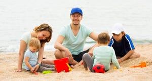 Familia feliz de cinco que se sientan en la playa arenosa Imagen de archivo libre de regalías