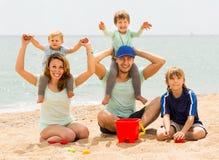 Familia feliz de cinco que sonríe en la playa del mar Imágenes de archivo libres de regalías