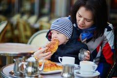 Familia feliz de dos en café al aire libre parisiense Fotos de archivo