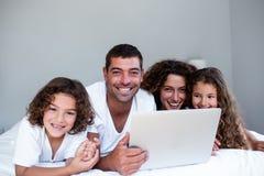 Familia feliz de familia usando el ordenador portátil junto en cama Fotos de archivo