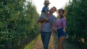 Familia feliz de granjeros con el pequeño hijo que camina en la huerta adentro durante la estación de la cosecha almacen de metraje de vídeo