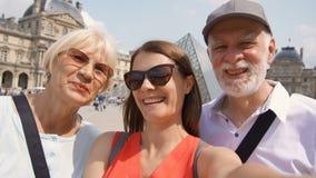 Familia feliz de hombre mayor y de mujer con la hija que toma el selfie en smartphone el vacaciones en París metrajes