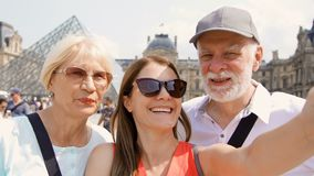 Familia feliz de hombre mayor y de mujer con la hija que toma el selfie en smartphone el vacaciones en París almacen de video