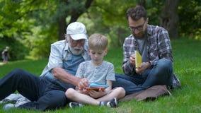 Familia feliz de la generación tres - el padre, el abuelo y el hijo rubio sentándose en hierba en el parque con los libros aprend almacen de video