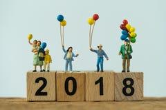 familia feliz de la gente miniatura que sostiene los globos que se colocan en woode Fotos de archivo