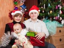 Familia feliz de la Navidad de celebración tres Fotografía de archivo libre de regalías