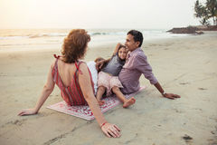 Familia feliz de la raza mixta con puesta del sol de la reunión del niño en la playa fotos de archivo libres de regalías