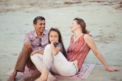 Familia feliz de la raza mixta con puesta del sol de la reunión del niño en la playa fotos de archivo