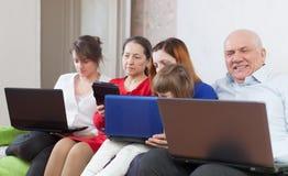 Familia feliz de los multigenerations con los ordenadores portátiles en casa Foto de archivo