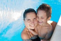 Familia feliz de madre y sonrisa y abrazo del niño en piscina azul en vacaciones de verano fotografía de archivo libre de regalías