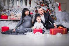 Familia feliz de mamá embarazada del regalo abierto de la Navidad imagen de archivo libre de regalías