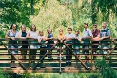 Familia feliz de once que se colocan en el puente en parque Fotografía de archivo libre de regalías