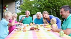 Familia feliz de siete que tienen comida junto Fotos de archivo libres de regalías