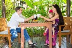 Familia feliz de té de consumición del padre, de la madre y del niño en la tabla en un día de verano Padres y niño del retrato en Foto de archivo libre de regalías