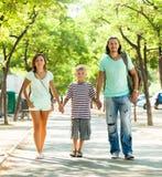 Familia feliz de tres con el adolescente que camina en parque Imagen de archivo libre de regalías