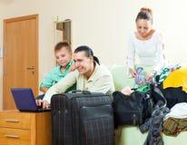 Familia feliz de tres con el adolescente que elige el centro turístico en el th Foto de archivo