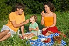 Familia feliz de tres en comida campestre en jardín Fotografía de archivo libre de regalías