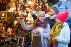 Familia feliz de tres en el mercado de la Navidad Imagenes de archivo