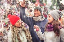 Familia feliz de tres en el mercado de la Navidad Fotos de archivo