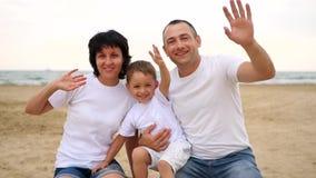 Familia feliz de tres en la mano arenosa de la playa del mar, de la sonrisa y el agitar a la cámara en la cámara lenta metrajes