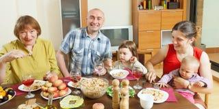 Familia feliz de tres generaciones que presenta sobre la tabla celebradora imagen de archivo