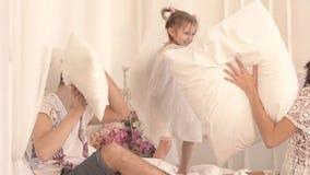 Familia feliz de tres: madre, padre e hija teniendo una lucha de almohada en cama almacen de metraje de vídeo