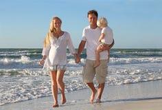 Familia feliz de tres personas que caminan en la playa a lo largo del océano Imágenes de archivo libres de regalías