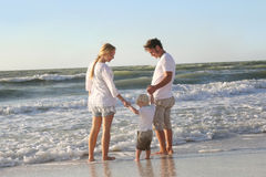 Familia feliz de tres personas que juegan en el océano mientras que Alon que camina Foto de archivo libre de regalías