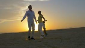 Familia feliz de tres que bailan en la playa en metrajes